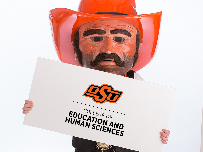 Pistol Pete holding a sign with the college name